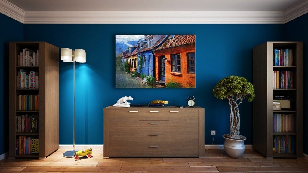 Blue painted wall with chest of drawers  and book rack place on that wall.