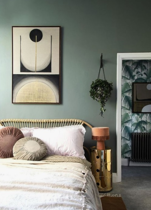 Green painted wall with wooden cot with white bedspread on it.