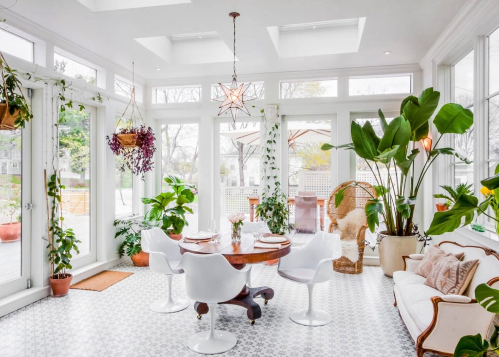 A lot of green plants in a white dining room, which increases the beauty of this home.