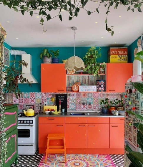 Bright orange cabinates in kitchen with green walls and plants all around