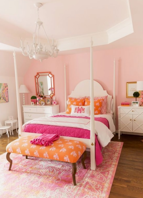 Light pink painted walls with white poster bed, white dresser on either side of bed.