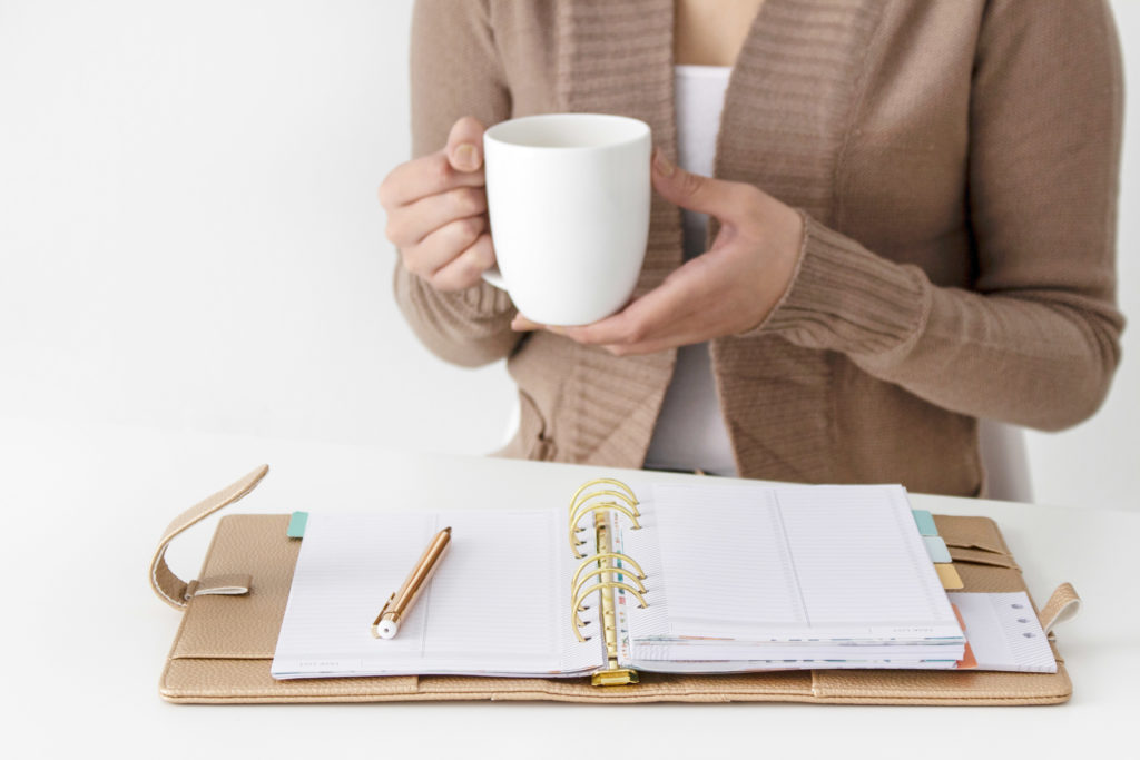 Girl with a coffee mug is sitting with her planner open