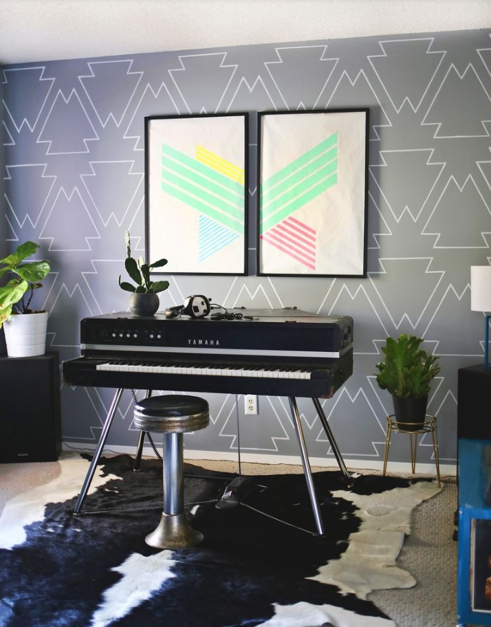 Grey wall with DIY stencil painting with keyboard in the front