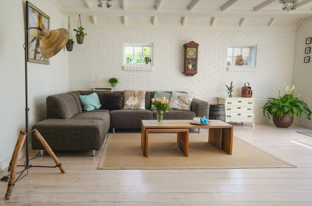 White living room with brown fabric sofa, wooden center table, white chest of drawers and planter in the corner.