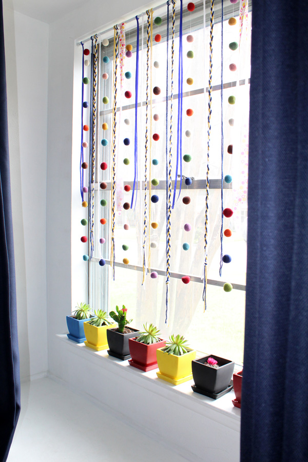 White window with colorful pots. Window is decorated with home made ribbon hangers.