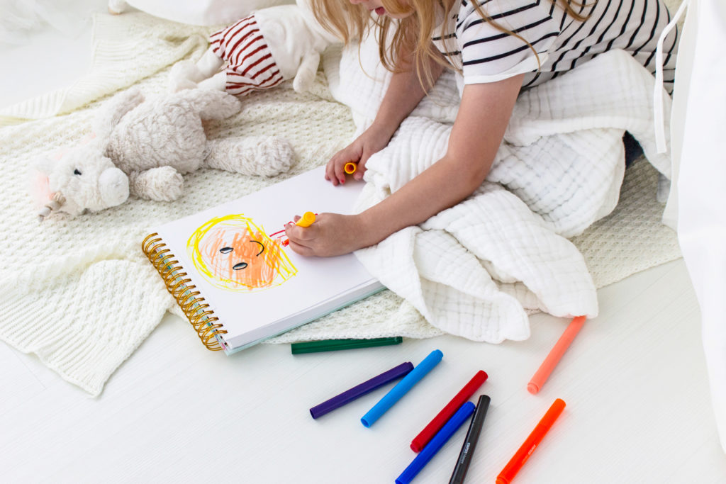 Kid drawing in book with color pens on floor next to her