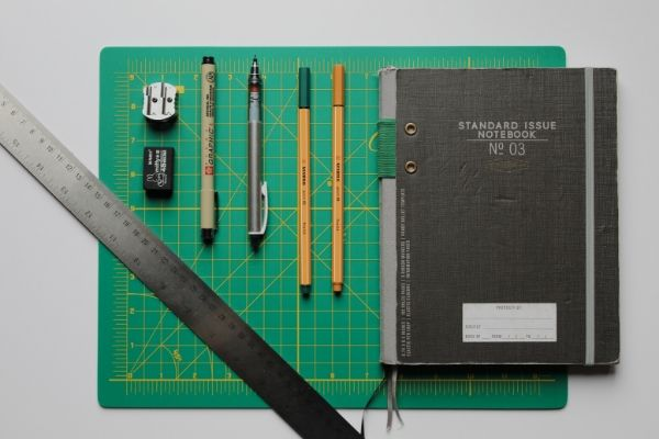 Flat lay of ruler, book and pencil