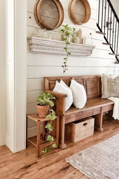 Wooden seating with cane side table with the paneled back wall at the entrance of a farm house