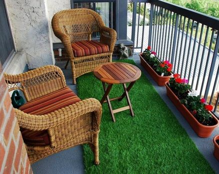 Small balcony with two cane arm chairs with wooden round table. Artificial grass on the floor