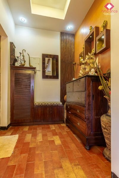 Foyer designed in Indian ethnic concept where we can see a wooden chest of drawers, shoe rack, niches and mirror.