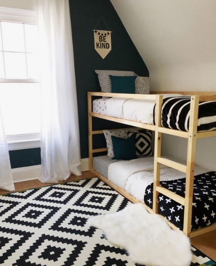A black and white kids bedroom with bunk bed and area carpet.
